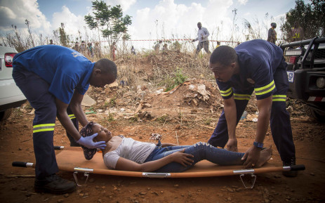 An injured woman is treated after she was injured after two commuter Metro Rail trains collided outside Tembisa. Picture: Thomas Holder/EWN