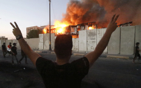 FILE: Iraqi protesters watch an official building in flames as they demonstrate against the government and the lack of basic services in Basra on 6 September 2018.  Picture: AFP