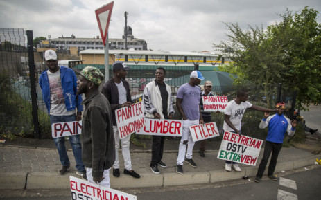 FILE: Unemployed builders, tilers and plumbers hold signs seeking jobs on the side of the road in South Africa. Picture: AFP