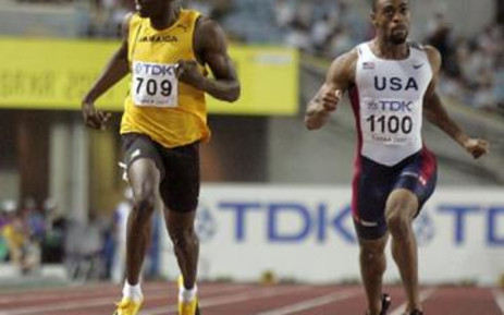 Fast feet: Usain Bolt (left) and Tyson Gay crash through the finish line at the 2007 World Championships. Picture: Gallo Images/AFP