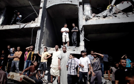 FILE: Palestinians gather on the rubble and shell of a building destroyed following an Israeli military strike, as they watch rescuers working in Rafah in the south of the Gaza Strip, on 21 August 2014. Picture: AFP.