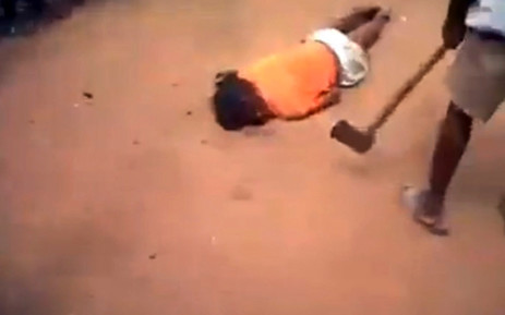 A screengrab from apparent cellphone footage which has gone viral showing a woman being kicked in the face, stomped on and beaten with an axe. Picture: Facebook.