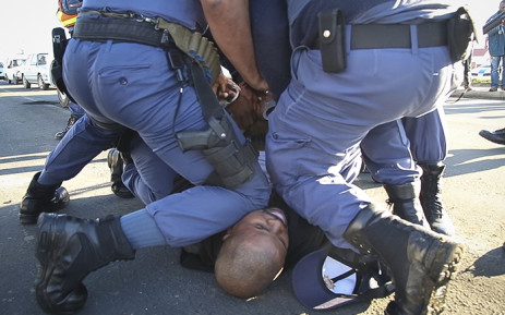 Police detain a taxi driver that resisted being taken in for questioning this morning in Thembalethu, George after drivers argued that a police road block, checking permits and roadworthiness was against their rights to do business. Picture: Thomas Holder/EWN