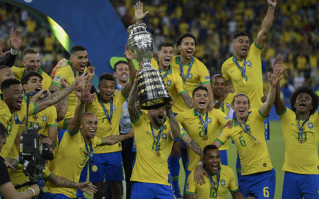Brazil's Dani Alves (C) raises the trophy as he celebrates with teammates after winning the Copa America after defeating Peru in the final match of the football tournament at Maracana Stadium in Rio de Janeiro, Brazil, on 7 July 2019. Picture: AFP
