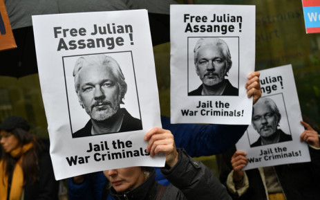 Demonstrators hold placards calling for WikiLeaks founder Julian Assange to be freed and not extradited to the US outside Westminster Magistrates Court in London on 21 October 2019 ahead of a case management hearing in Assange's case. Picture: AFP