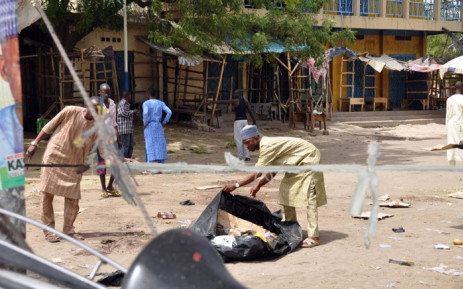 A man tries to gather traces of the blasts in Maiduguri on 7 March, 2015. Three bombings in northeast Nigeria's largest city of Maiduguri killed 58 people and wounded 139 others, the area police chief said. Picture: AFP.