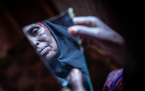 Amran Mahamood, who has made a living for 15 years by circumcising young girls, looks into a piece of a mirror on 19 February, 2014 in Hargeysa. Picture: AFP.