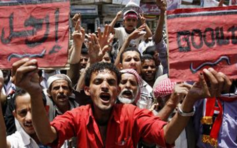 "A Yemeni anti-government protester holds signs that read in English and Arabic ""Go Out"" and ""Leave"" during a demonstration calling for the ouster of President Ali Abdullah Saleh in Sanaa on 30 May 2011. AFP"