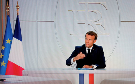 This picture shows a screen displaying French President Emmanuel Macron as he addresses the nation during a televised interview from the Elysee Palace concerning the situation of the novel coronavirus COVID-19 in France, in Paris on 14 October 2020. Picture: AFP