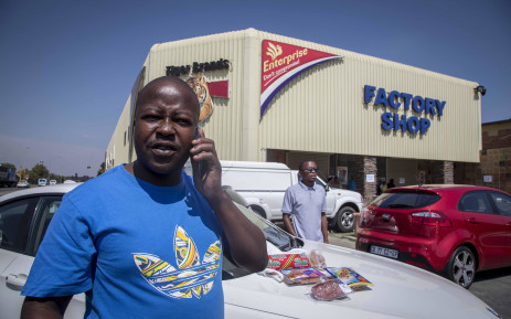 FILE: A man drops meat hampers - packets containing multiple products that cost roughly R200 - with security officials outside the Enterprise factory in Germiston. Picture: Thomas Holder/EWN