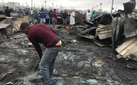 A Dunoon resident hard at work clearing the site following a fire that left about 500 homeless on 13 March. Picture: Shamiela Fisher/EWN