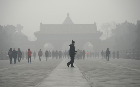 An elderly man walks in front of a group of people during heavy smog at the Temple of Heaven park in Beijing on 20 December, 2016. Picture: AFP.