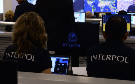 Interpol agents monitor an operation. Picture: AFP