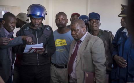 Police check their warrant list with those inside the MDC HQ, some of whom were still hiding from the violence of the army from the day before. Picture: Thomas Holder/EWN.