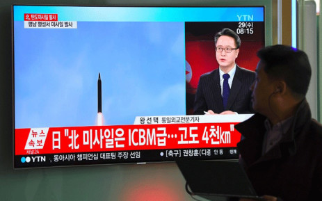 A man walks past a television screen showing a file video footage of North Korea's missile launch, at a railway station in Seoul on 29 November, 2017. Picture: AFP.