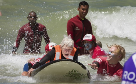 Pamela Hanford (75) is helped by a team of coaches and volunteers to surf at an adaptive surfing event at Muizenberg beach, on 20 January 2019, in Cape Town, South Africa. Picture: AFP