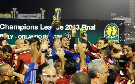 Al Ahly coach Mohamed Youssef holds up the African Champions League trophy in Cairo on 10 November 2013. Picture: AFP