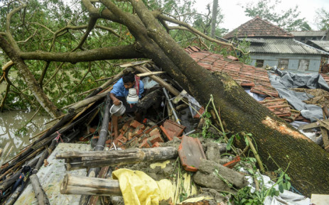 A man salvages items from his house damaged by cyclone Amphan in Midnapore, West Bengal, on 21 May 2020. Picture: AFP