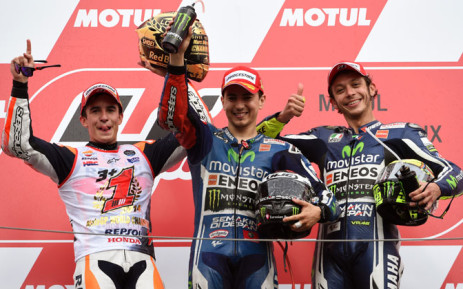 Japanese Grand Prix winner Movistar Yamaha MotoGP rider Jorge Lorenzo of Spain (C) poses with second placed Repsol Honda Team rider Marc Marquez of Spain (L) and third placed Movistar Yamaha MotoGP rider Valentino Rossi of Italy (R) on the podium at the MotoGP Japanese Grand Prix in Motegi, Tochigi prefecture on 12 October 2014. Picture: AFP/TOSHIFUMI KITAMURA