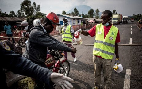 A motor taxi driver gets his hands washed at an Ebola screening station on the road between Butembo and Goma on 16 July 2019 in Goma. Picture: AFP