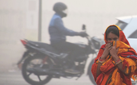 FILE: An Indian girl with her face covered walks on a street amid heavy smog in New Delhi on 13 November 2017. Picture: AFP