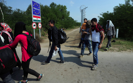 FILE: Migrants cross into Hungary from Serbia next to the 4m tall border fence at the crossing point near the village of Asotthalom. Picture: AFP