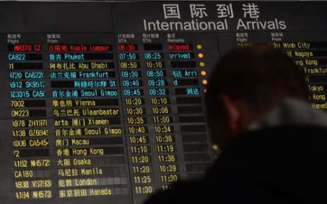 FILE: A man stands beside the arrival board showing the flight MH370 (top-red) at the Beijing Airport after news of the Malaysia Airlines Boeing 777-200 plane disappeared on 8 March 2014. Picture: AFP.