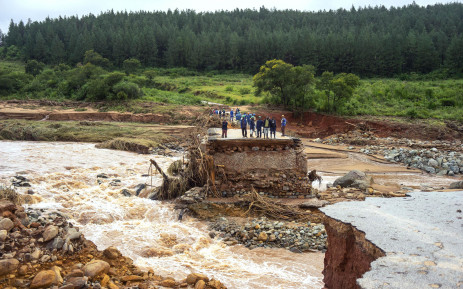 Timber company workers stand stranded on a damaged road on 18 March 2019, at Charter Estate, Chimanimani, eastern Zimbabwe, after the area was hit by the cyclone Idai.  Picture: AFP