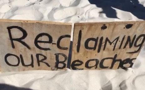 "A ""Reclaiming Our Beaches"" board is erected at Clifton 4th Beach in Cape Town during a sit-in by activists. Picture: EWN."
