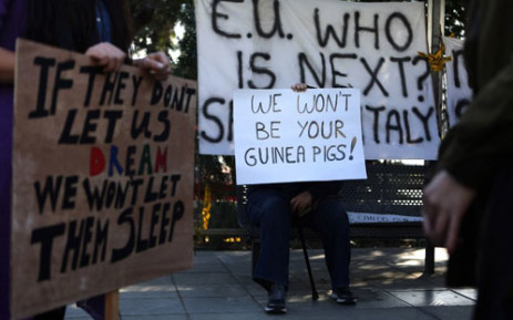 Cypriots hold placards during a protest against an EU bailout deal outside the parliament in Nicosia on March 18, 2013. Picture: AFP/ PATRICK BAZ