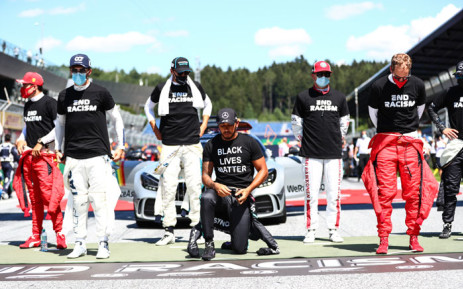 """Mercedes driver Lewis Hamilton (C) kneels ahead the Austrian Formula One Grand Prix race on 5 July 2020 in Spielberg, Austria in solidarity with the """"Black Lives Matter"""" movement. Picture: AFP"""