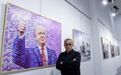 """Albanian artist Avni Delvina poses for a photo in front of his paintings during the exhibition 'The Donald' in Tirana on February 21, 2019. Donald Trump as Rambo or as Jesus crucified: a painter dedicated fifty paintings to the American president, his """"idol"""", which are on display in the Albanian capital. Picture: AFP."""