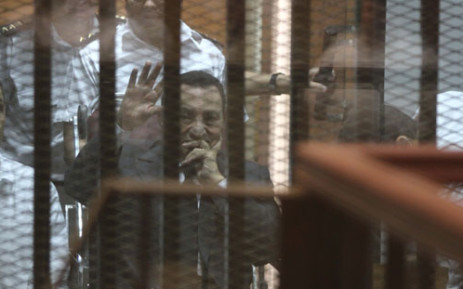 FILE:Egypt's deposed president Hosni Mubarak waves from behind the accused cage during his trial on 21 May, 2014 in Cairo. Picture: AFP.