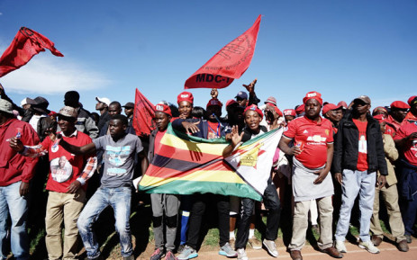 Movement for Democratic Change Alliance (MDC) supporters hold MDC and Zimbabwe flags as they gather to listen to their leader Nelson Chamisa during an election campaign rally on 21 July, 2018 at White City stadium in Bulawayo, Zimbabwe. Picture: AFP