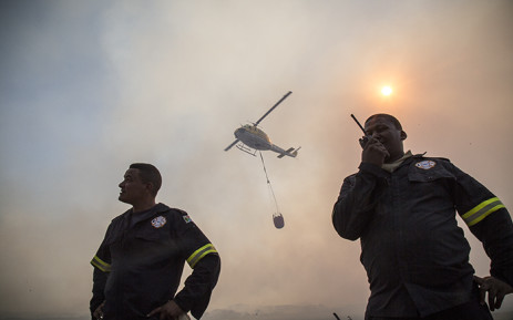 Two firefighters radio on the front lines of the fire while a helicopter prepares to water-bomb the raging flames. Picture: Thomas Holder/EWN
