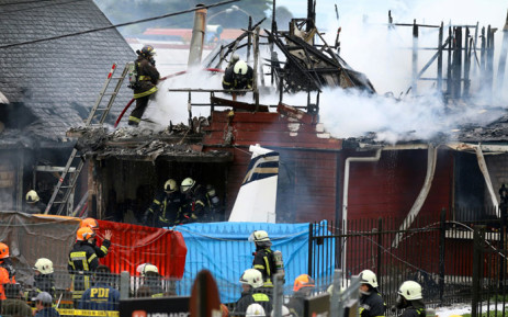 Picture released by Aton Chile showing firefighters working at the scene after a light aircraft crashed into a house in Puerto Montt after taking off from La Paloma aerodrome, about 1000 km south of Santiago on 16 April 2019. Picture: AFP
