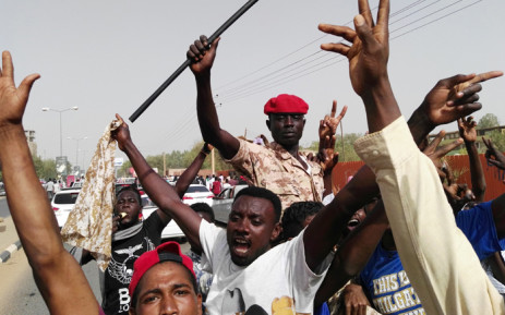 Sudanese men chant slogans as a soldier imitates President Omar al-Bashir waving his trademark cane, on 11 April 2019 during a rally in the capital Khartoum. Picture: AFP