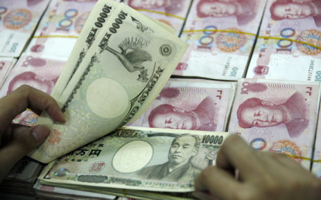 FILE: A Chinese bank clerk shows off 10000 Japanese Yen notes among the stacks of 100 yuan notes, at a bank in Huaibei, east China's Anhui province on 29 May 2012. Picture: AFP.