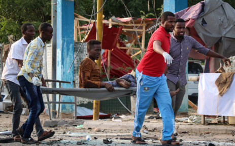 People rescue a wounded person following three blasts of suicide bomb car attacks in Mogadishu, on 9 November 2018. Picture: AFP.
