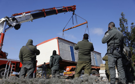 Members of the Israeli security forces remove a caravan that settlers had brought to the former outpost of Amona near the Jewish settlement of Ofra, following clashes as dozens of settlers were evicted early on 3 January 2019 from the former outpost in the occupied West Bank. Picture: AFP