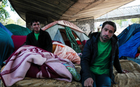 Mounir (R), a 28-year-old man from Pakistan, sits on a mattress under a bridge at a migrant and refugee makeshift camp set up under the highway near Porte de la Chapelle, northern Paris, on 19 April 2017. Picture: AFP.