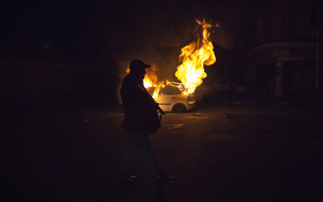A police officer walks pass a burning car in Jeppestown during xenophobic violence on 16 April 2015. Picture: Thomas Holder/EWN