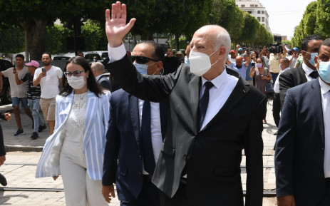 (FILES) In this file handout picture provided by the Tunisian Presidency's official Facebook Page on August 1, 2021 shows President Kais Saied (C) gesturing as he walks protected by security while touring through Habib Bourguiba avenue in the centre of the capital Tunis. TUNISIAN PRESIDENCY / AFP