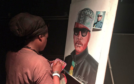 """Celebrity funeral artist Lebani Sirenje doing a portrait of Jabulani Tsambo also known as """"Jabba"""" in front of the stage at the Newtown Music Factory in Johannesburg. Picture: Katleho Sekhotho/EWN."""