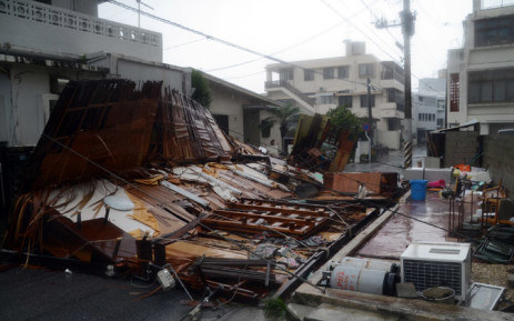FILE: A wooden house collapsed during strong winds in Naha on Japan's southern island of Okinawa on 8 July 2014. Powerful typhoon Neoguri lashed Japan's southern Okinawa islands on 8 July, forcing over half a million people to seek shelter. Picture: AFP.