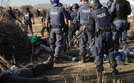 FILE: Police look down at dead mineworkers who were protesting at Lonmin's Marikana mine on 16 August 2012 for more wages. Picture: EWN.