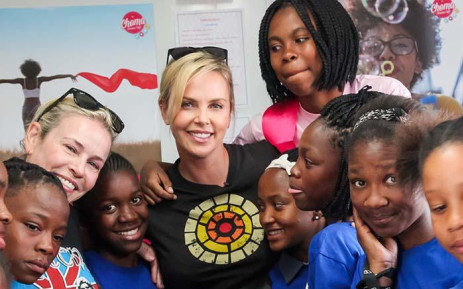 Charlize Theron with girls from the Choma Dreams Café.  Picture: CTAOP
