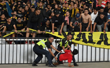 This file photo taken on 5 September 2019 shows policemen detaining a supporter of Indonesia next to supporters of Malaysia (in black) after an incident during their 2022 Qatar World Cup preliminary qualification round 2 football match at the Gelora Bung Karno stadium in Jakarta. Picture: AFP