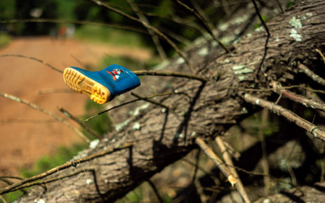 A picture taken on 20 March 2019 shows a child's plastic boot hanging on a fallen tree by the roadside of Ngangu township, in Chimanimani, as some parents are still searching the area in the hope that they will find the bodies of their missing children, following cyclone Idai. Picture: AFP