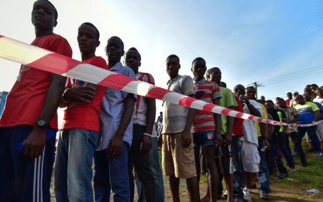 People wait in line prior to casting their vote for Liberia's presidential and legislatives elections at a polling station in Monrovia on 10 October 2017. Picture: AFP.
